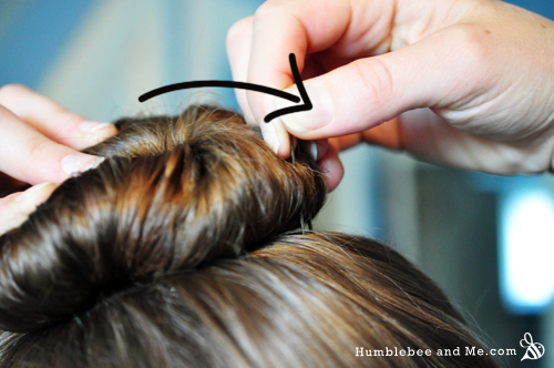 Flip the pin downwards at the curved end, levering the tips so they point into the bun.