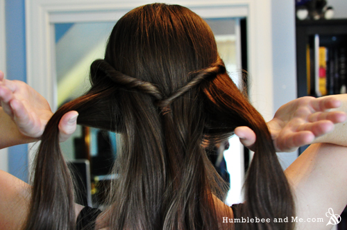 Start by dividing your hair into three sections for a braid leaving the tail from the twist ponytail in the middle section.