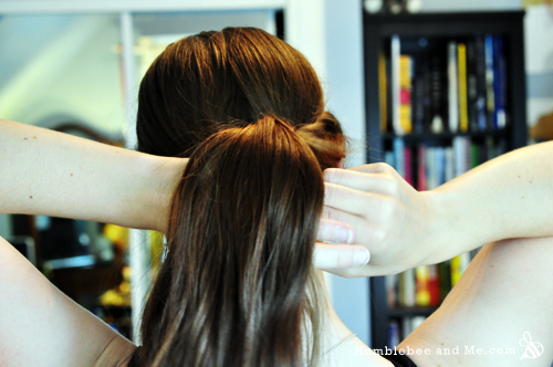 You're just going to do the twisting thing with all your hair now—gather it all up and feed it up and through the twisty ponytail, and then down through at the nape of your neck.